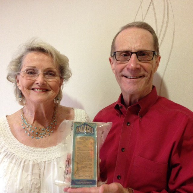 Darlene Flatt (left) and Warren A. Perrin, chairman of the Acadian Museum.  The bottle of Hadacol that Perrin is holding was given to Flatt by her employer in 1951, along with her last pay check.  The special–and perhaps last–Hadacol bottle was donated to