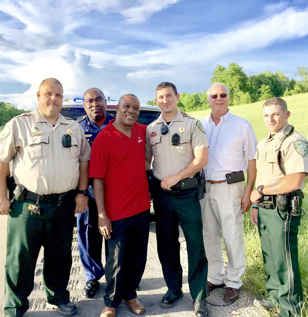 Father Julius Ohiaege takes photo with law enforcement who helped him / Diocese of Lafayette