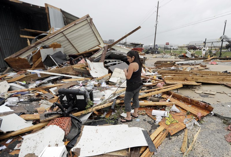 Jennifer Bryant looks over the debris from her family business destroyed by Hurricane Harvey Saturday, Aug. 26, 2017, in Katy, Texas. AP Photo/David J. Philip