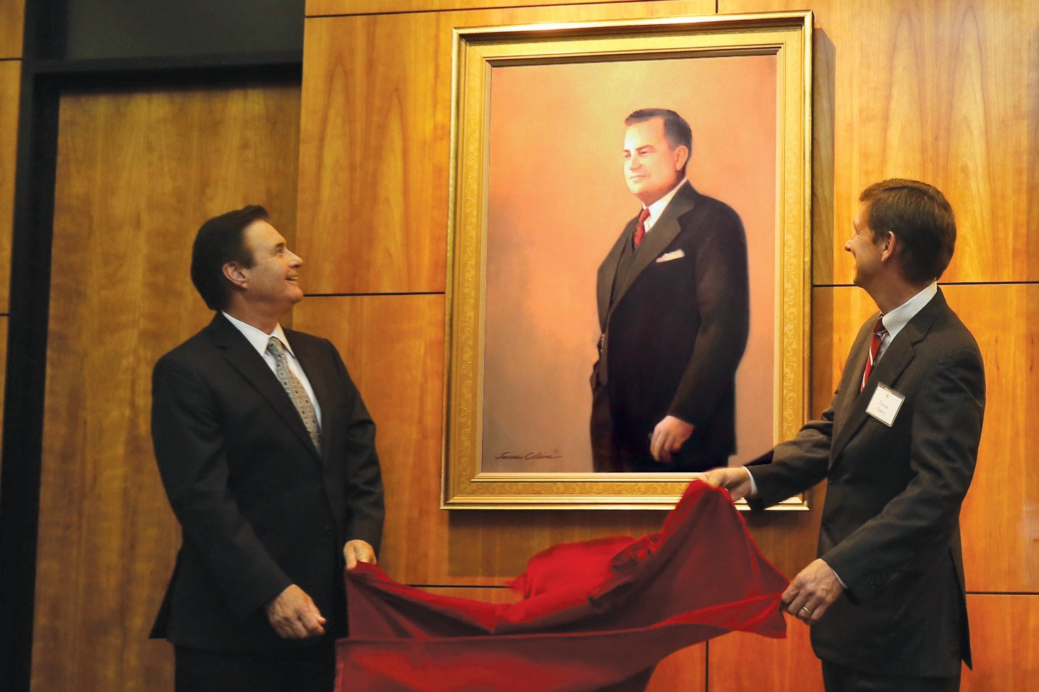 John Bloom, left, vice president for University Advancement, and Thomas Chance, UL Lafayette Foundation board of trustees member, present a portrait of Lether Frazar, the University's second president. Portraits of the University's five former preside