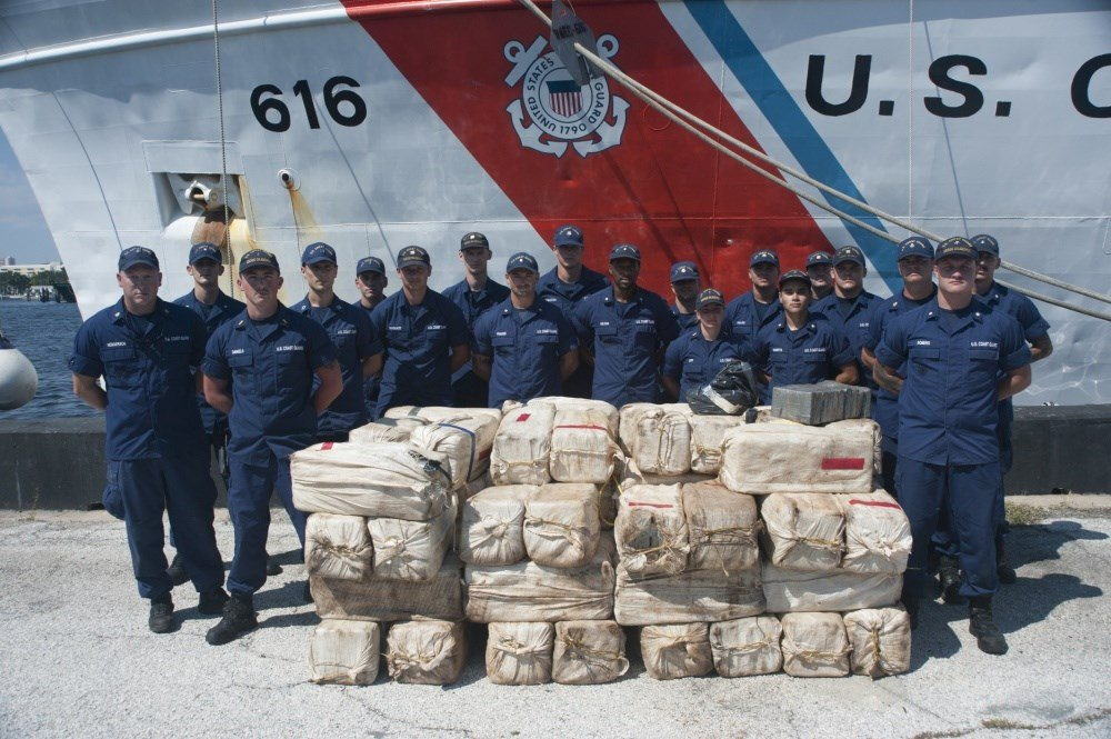 Coast Guard Cutter Diligence crewmembers stand next to more than 1,800 kilograms of cocaine in front in St. Petersburg, Florida / Petty Officer 2nd Class Ashley J. Johnson