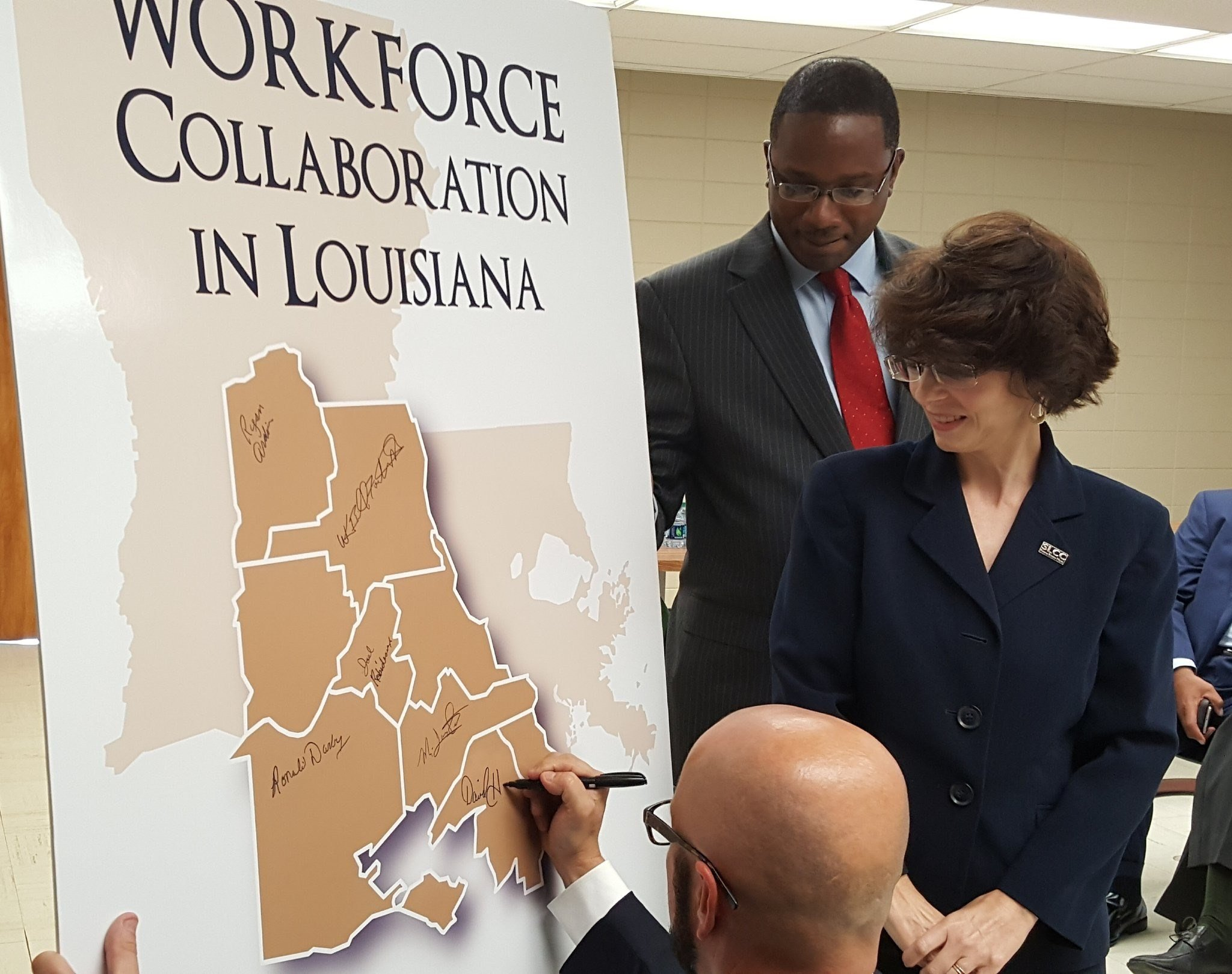 David Hanagriff, St. Mary Parish President, signs a workforce collaboration agreement during a press announcement at SLCC's T.H. Harris Campus. SLCC Chancellor Dr. Natalie Harder is pictured along with SLCC's Associate Vice President of Economic and Workf