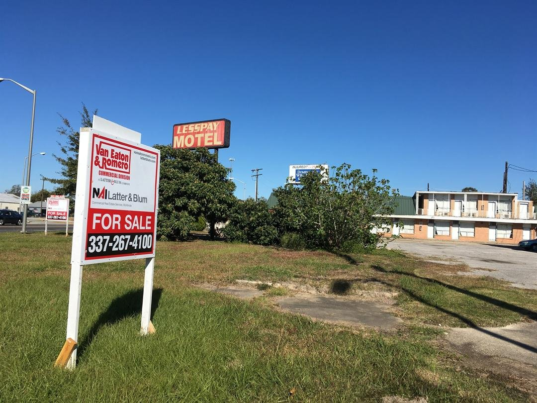 A for-sale sign stands outside the shuttered LessPay Motel at Lafayette's Four Corners on Nov. 28, 2017. Lanie Lee Cook/KATC