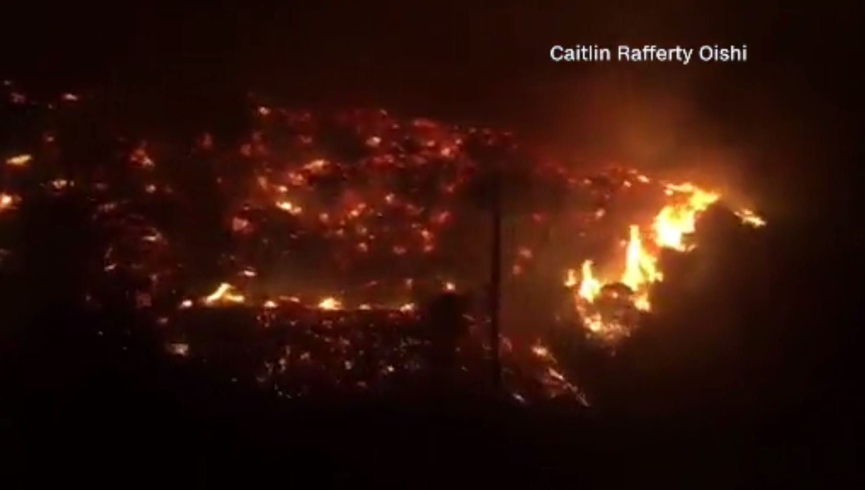 Flames burning on the hillside as cars drive down the 405 Freeway in Los Angeles County, CA  / CNN
