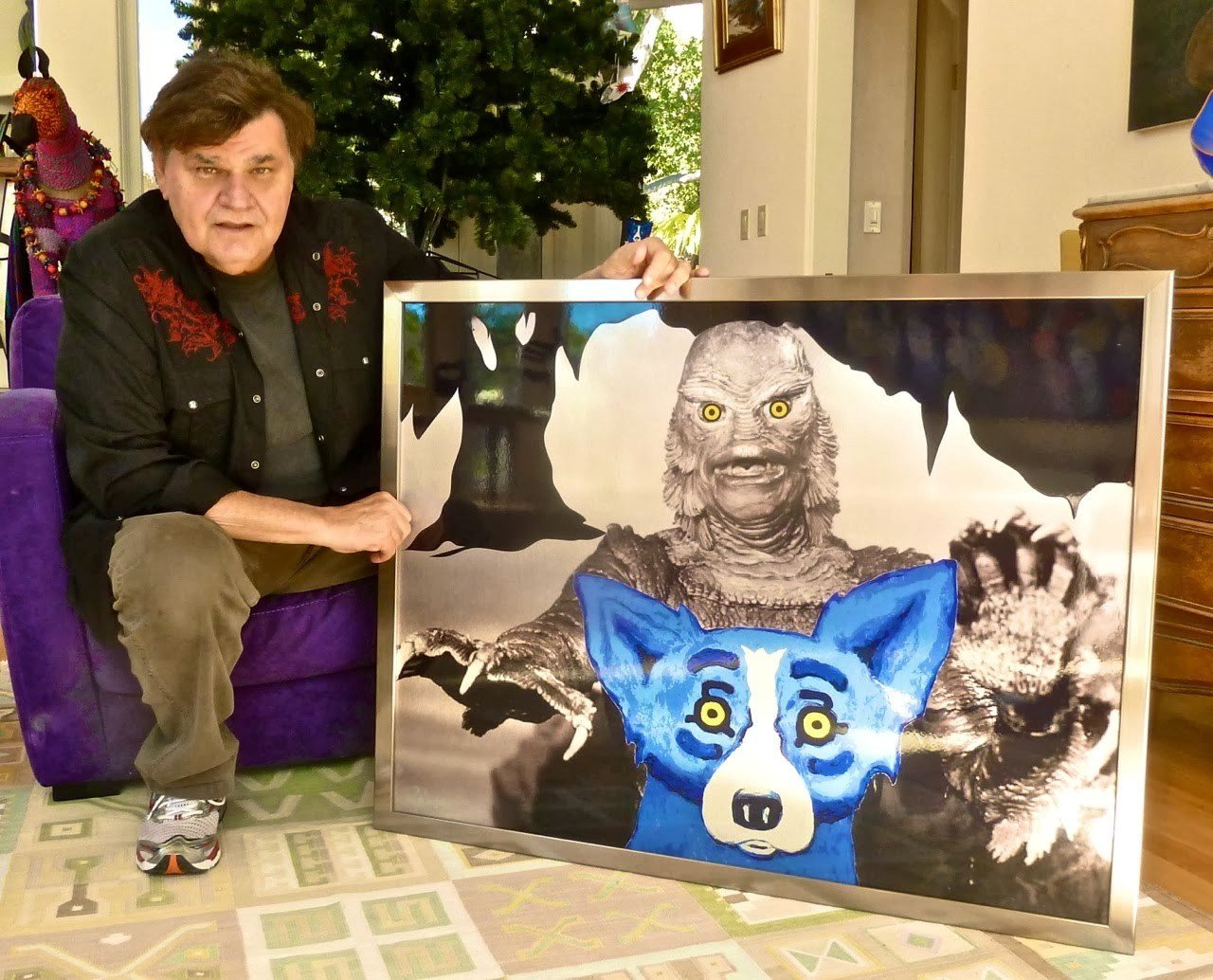 George Rodrigue pictured with one of his paintings from the Blue Dog series, featuring the Loup-garou monster / Courtesy: Ally Hodapp with Bond Moroch