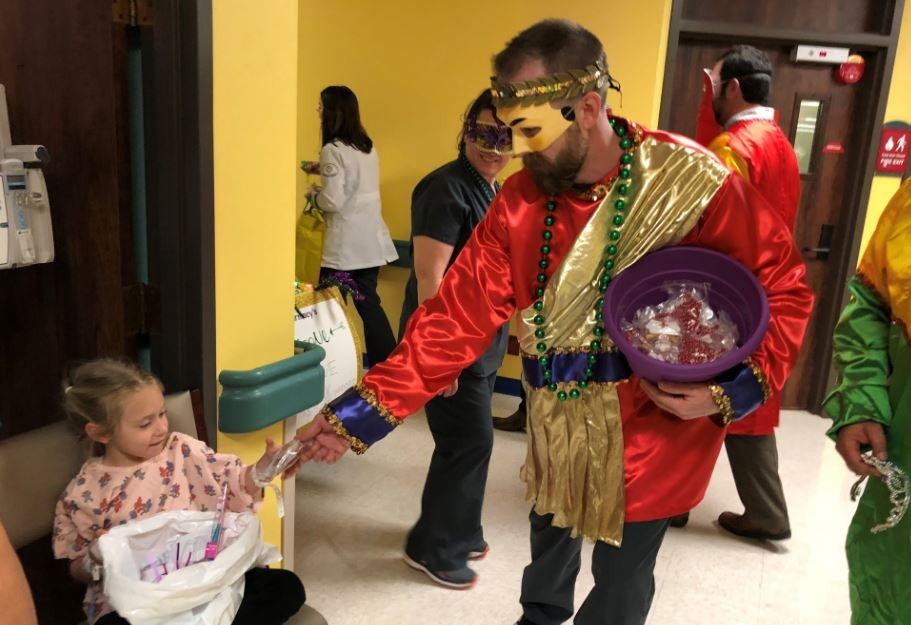 A Mardi Gras with the Krewe of Gabriel hands beads to Rylee Romero, 4, at Women's & Children's Hospital during the sixth annual Mardi Gras parade Friday, Feb. 9.
