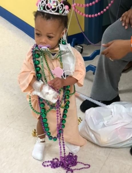Kinsley Cormier, 18 months, shows off her tiara and bead collection during the sixth annual Mardi Gras parade Friday, Feb. 9 at Women's & Children's Hospital.