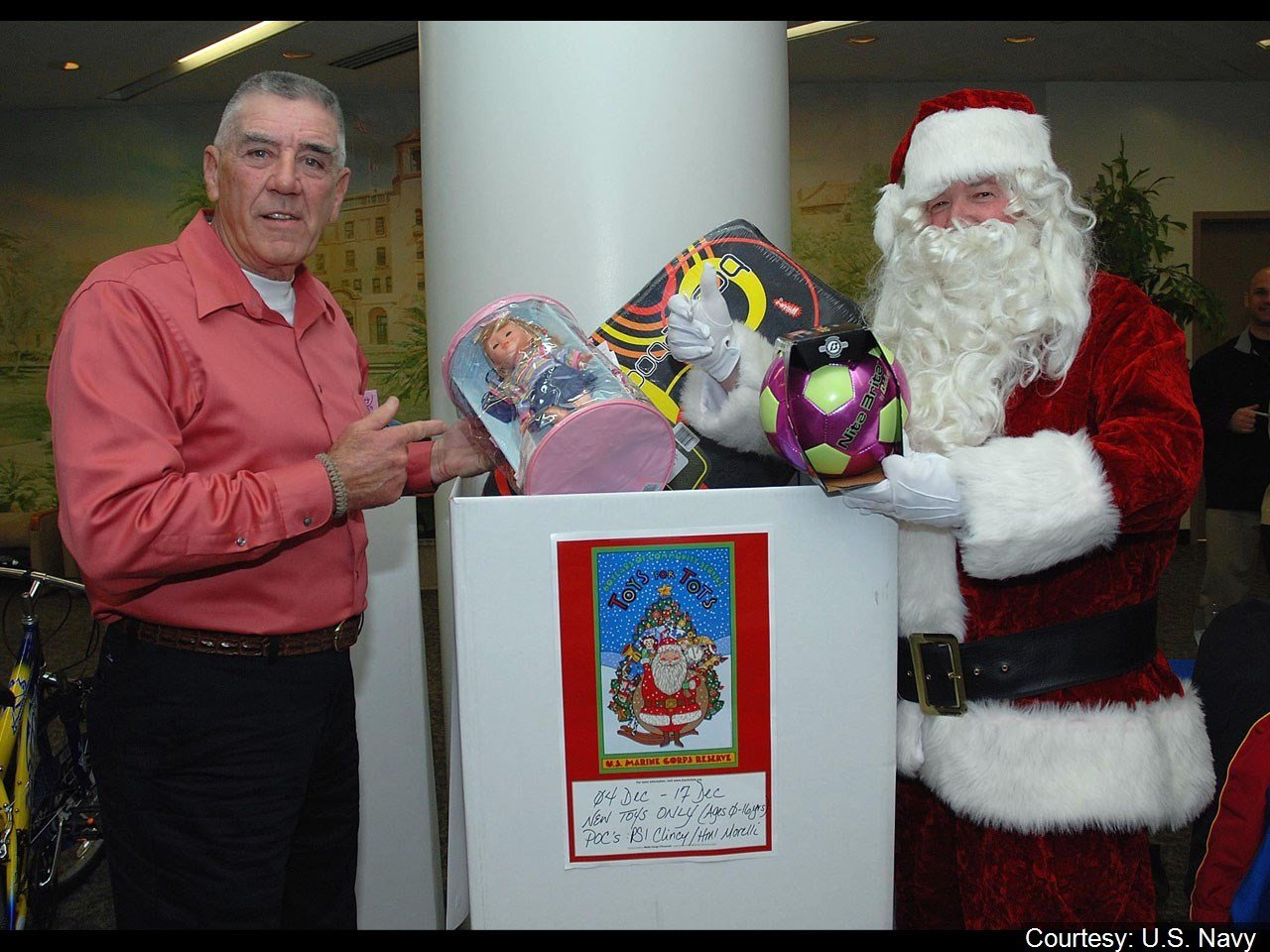 Former U.S. Marine Corps drill instructor turned actor R. Lee Ermey, left, joins Santa Claus to put toys into the Toys for Tots donation box at Naval Medical Center San Diego/ MGN Online